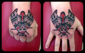 Death moth hand tattoo