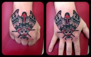 Death moth hand tattoo